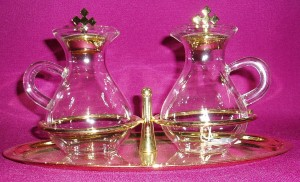 Glass cruet set on a tray, with gold tops on the glasses.