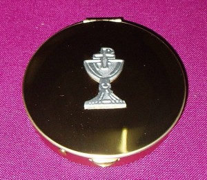 Gold pyx with chalice motif on the lid; holds approx 20 wafers.